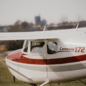 an image of a white cessna 172 plane with red and gray striping