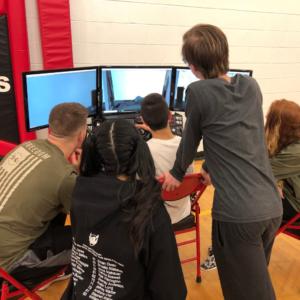 five students at the open air flight club study a flight simulator