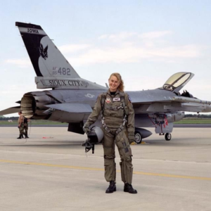 a female fighter pilot out of iowa stands in front of her jet