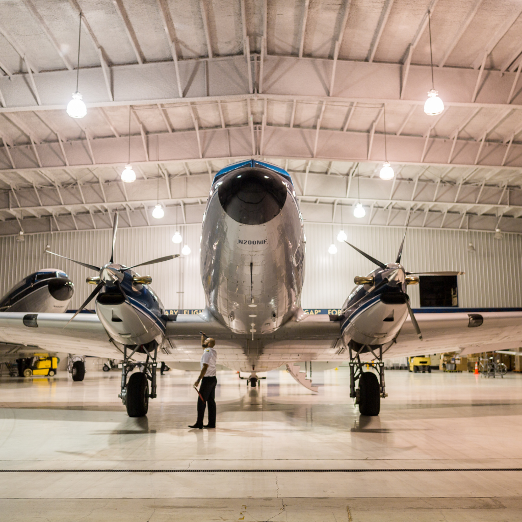 a commercial pilot examines his plane in the airplane hanger prior to take off