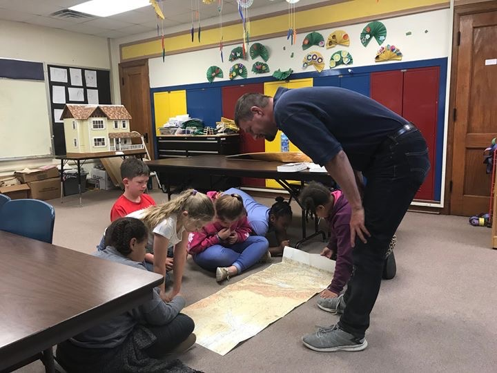 Jeff Jorgenson, Founder of Open Air Flight Club reviews a map in a classroom with students. The map is spread out on the floor and 6 young children are huddled around it. Aviation and flight can teach us so much about the world and how we enter it.