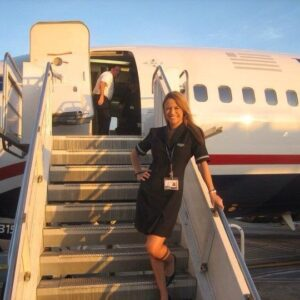 A flight attendant stands on the stairs of a small passenger plane.