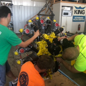 Open Air Flight Club members work on the engine of a plane