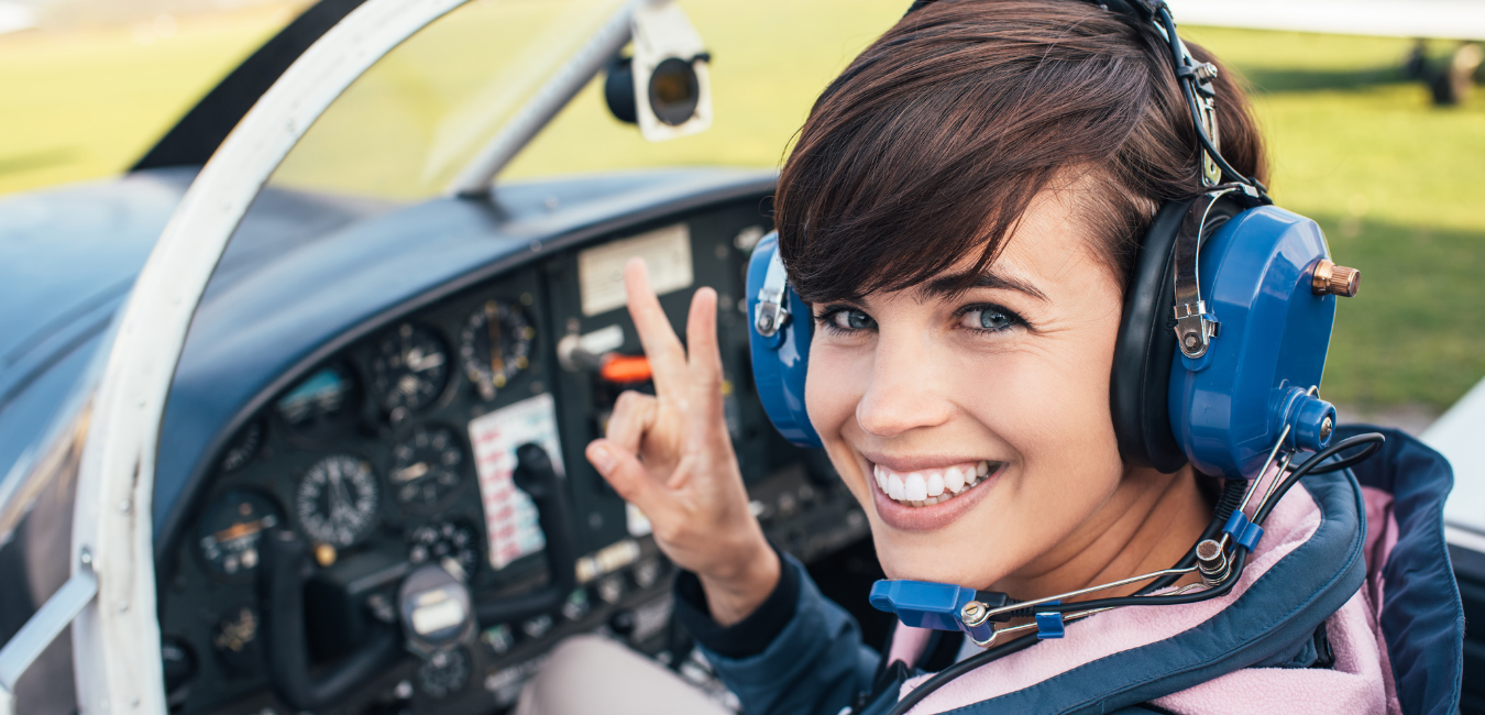 A young woman flashes the peace sign as she prepares for take off in a small private plane