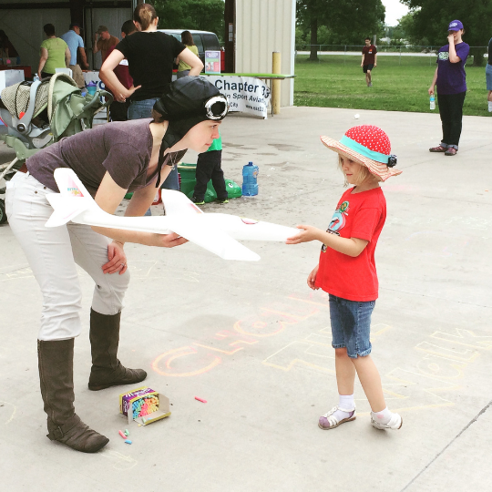 a young woman holding a model airplane and wearing a flight club talks to a younger girl about flying