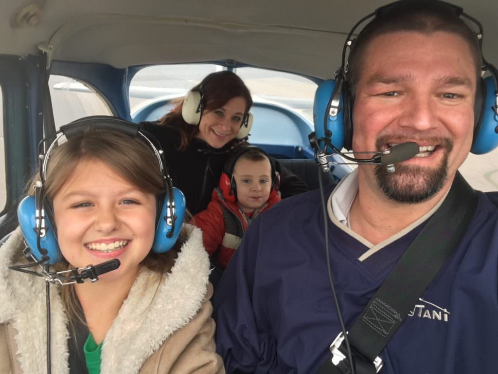 Jeff Jorgenson, Founder of Open Air Flight Club taking off with his daughter in the front seat of their plane and his wife and young son in the back seat.