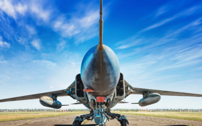 a jet sitting on the runway under a blue sky