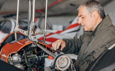a mechanic works on the engine of his plane