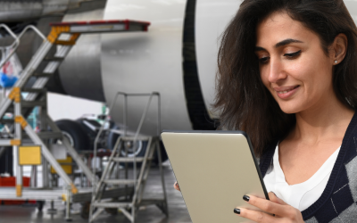 a woman holds a tablet in an airplane hanger