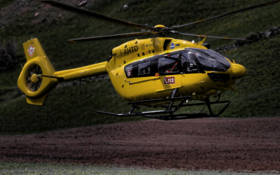 a yellow helicopter sits on a ridge